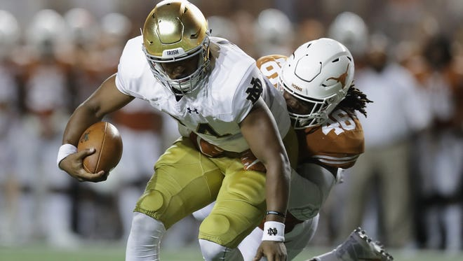 AUSTIN, TX - SEPTEMBER 04:  DeShone Kizer #14 of the Notre Dame Fighting Irish runs with the ball as Malik Jefferson #46 of the Texas Longhorns attempts to tackle him during the second half at Darrell K. Royal-Texas Memorial Stadium on September 4, 2016 in Austin, Texas.  (Photo by Ronald Martinez/Getty Images)