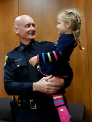 Green Bay Police Chief Andrew Smith picks up his daughter Katherine, 3, before his swearing in ceremony in the City Council chambers at City Hall.