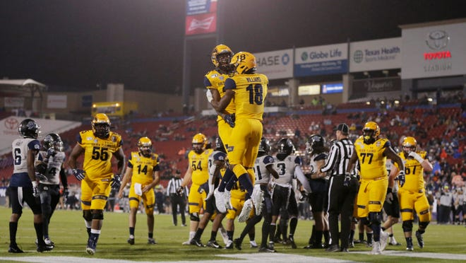 Kent State running back Xavier Williams (No. 18) and wide receiver Isaiah McKoy (No. 23) celebrate a touchdown during last December's Frisco Bowl victory over Utah State. Golden Flashes players who have been living in the Northeast Ohio area will be permitted to return to campus for voluntary conditioning drills starting Monday.