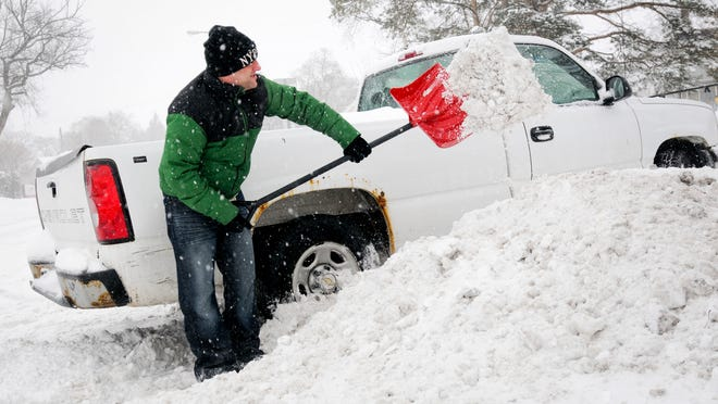 Port Huron resident Steve Krueger helps get his brother's car out of the snow in his driveway on Electric Avenue in Port Huron.