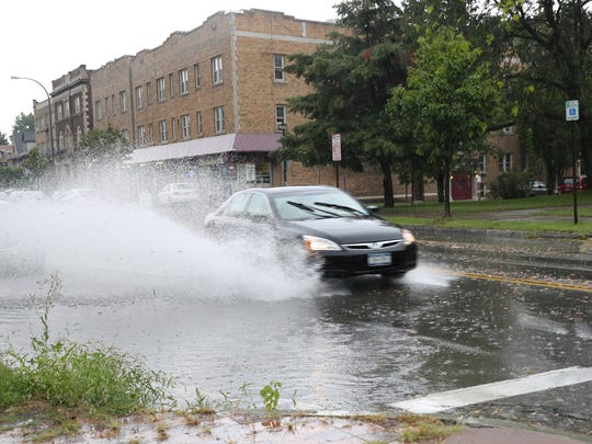 Cars splash through puddles on Monroe Avenue on Tuesday, Aug. 22 after severe weather warning.