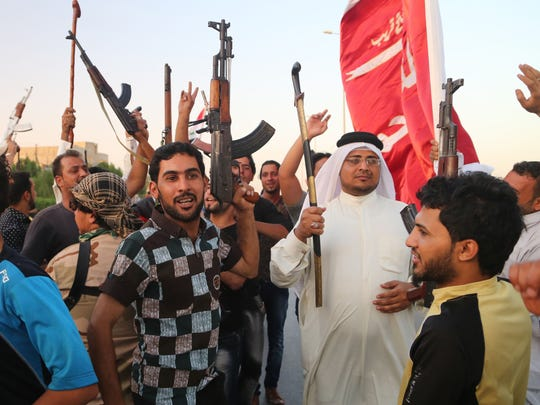 Shiite tribal fighters raise their weapons and chant slogans against the al-Qaida-inspired Islamic State of Iraq and the Levant (ISIL) in Basra, Iraq's second-largest city, 340 miles (550 kilometers) southeast of Baghdad, Iraq, Sunday, June 15, 2014. Emboldened by a call to arms by the top Shiite cleric, Iranian-backed militias have moved quickly to the center of Iraq's political landscape, spearheading what its Shiite majority sees as a fight for survival against Sunni militants who control of large swaths of territory north of Baghdad.
