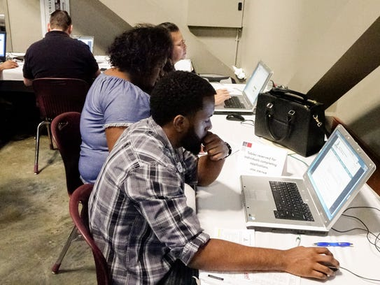 Jobseekers fill out applications during the Lafayette