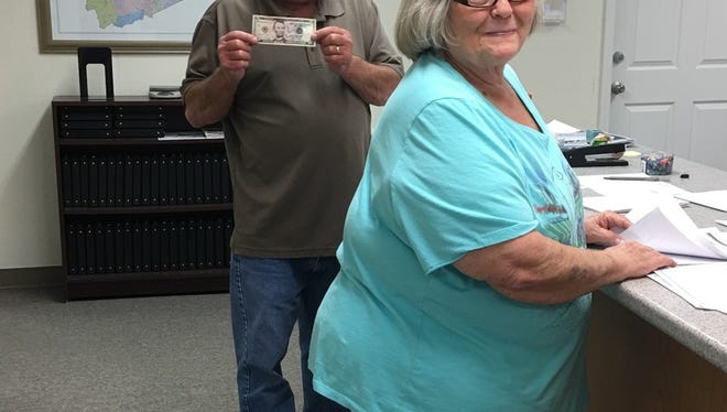 Current Marshall Mayor Jack Wallin, holding a $5 bill for his filing fee, and Alderman Billie Jean Haynie arrived at the Board of Elections office shortly after the candidate filing period opened at noon July 7.