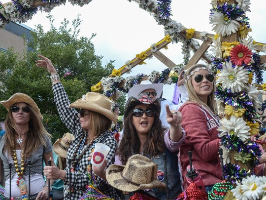 Members of the Krewe of Daisy Dukes throw beads to the crowd during the 2016 Grand Mardi Gras Parade in downtown Pensacola. The parade returns Saturday.