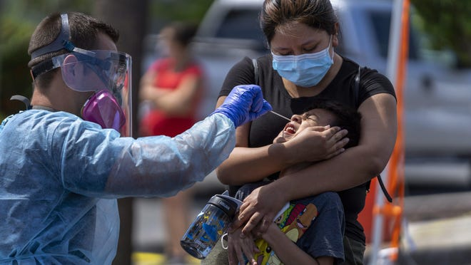 Lily Ramirez holds her son Noel Ramirez, 6, as he gets tested for COVID-19 by Palm Beach County Fire Rescue EMT Aaron Longchamps at a mobile testing site at the Osborne Community Center in Lake Worth Beach, Florida on May 22.