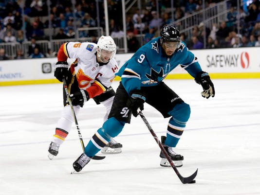 FILE - In this March 24, 2018, file photo, San Jose Sharks' Evander Kane (9) skates in front of Calgary Flames' Mark Giordano during the second period of an NHL hockey game in San Jose, Calif. Kane is excited for his first chance at the postseason after 574 career games when the Sharks open their first-round series in Anaheim on Thursday, April 12, 2018. (AP Photo/Marcio Jose Sanchez, File)