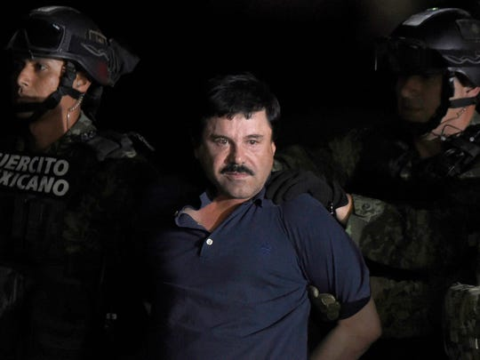 "In this file photo taken on Jan. 8, 2016, drug kingpin Joaquin ""El Chapo"" Guzman is escorted into a helicopter at Mexico City's airport following his recapture during an intense military operation in Los Mochis, in Sinaloa State."