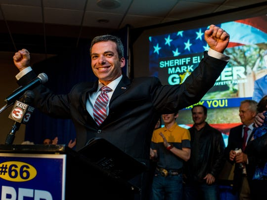 Mark Garber raises his hands in celebration as he delivers his victory speech after defeating Scott Police Chief Chad Leger in the run-off election for Lafayette Parish Sheriff during at River Oaks Event Center in Lafayette, La., Saturday, Nov. 21, 2015.