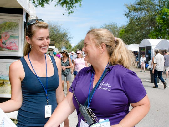 Carly Mejeur, at left, talks with Rebecca Selig, who has worked with Arti Gras for 11 years and says she loves seeing the progression of the festival.