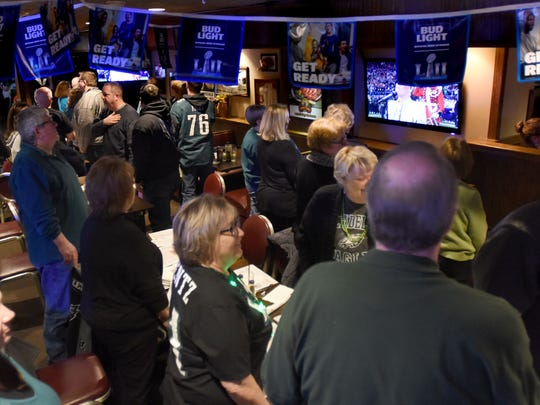 Patrons at Stanley's standing during the National Anthem before the start of Super Bowl 52.