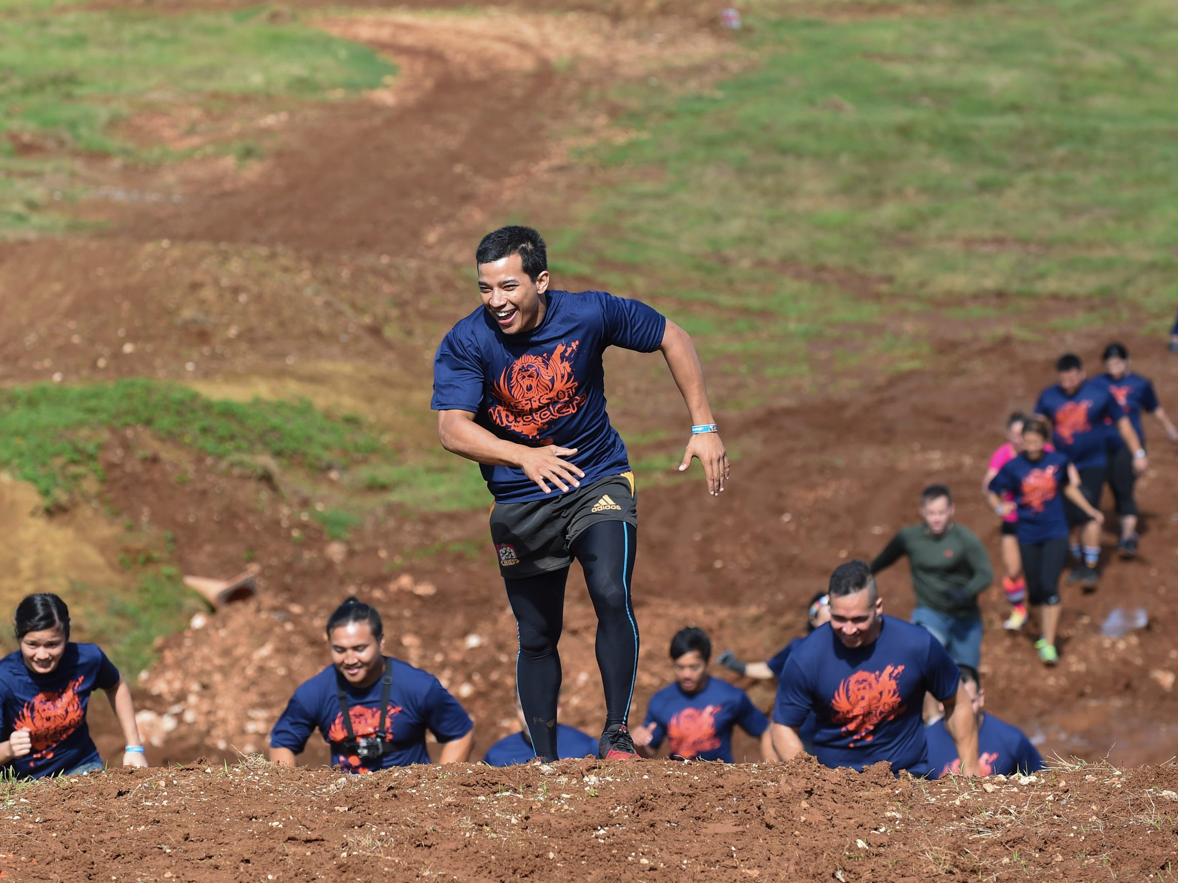 "Team Metgot Mudders make their way up the muddy hills of ""Dirtbike Alley"" in the KONQER Obstacle Course Race at the Jose and Herminia Memorial Off-Road Park in Yigo on Nov. 29."