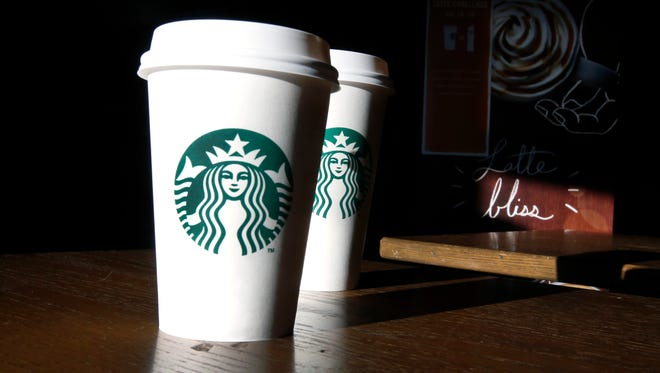 Starbucks cups are shown mugs in a cafe in North Andover, Mass.