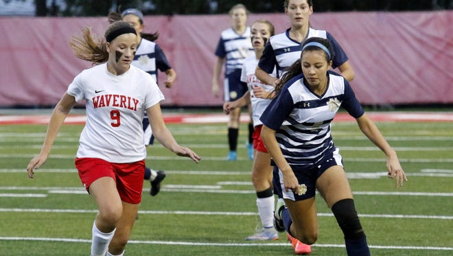 Waverly's Cora Smith, left, and Elmira Notre Dame's Laurel Vargas try to gain possession Tuesday night during an IAC South Large School tiebreaker at Waverly Memorial Stadium.