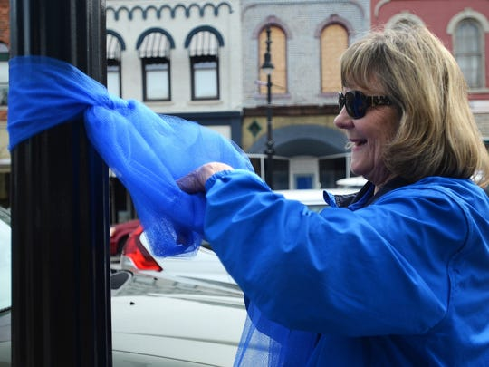 Staff from the St. Clair County Child Abuse and Neglect Council hang up blue ribbons in support of Child Abuse Prevention Month.