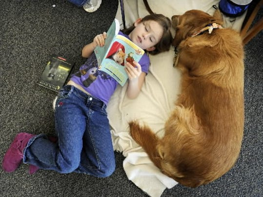 Scarlett Garman, then 8, of Spring Grove lays with Annie as she reads aloud to the dog during the Tales for Tails therapy dog program at Glatfelter Memorial Library in Spring Grove in 2012. (FILE PHOTO)