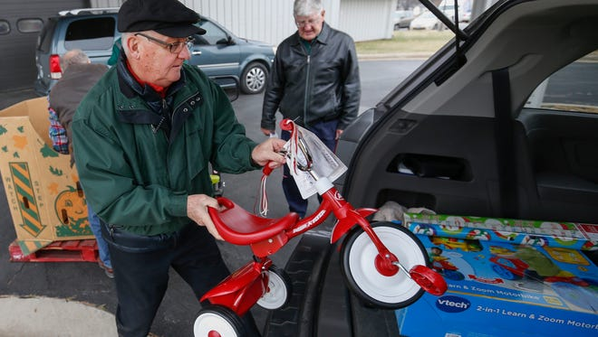 Brad Hoppes loads a tricycle into the back of a vehicle for Share Your Christmas at Crosslines on Friday, December 16, 2016.