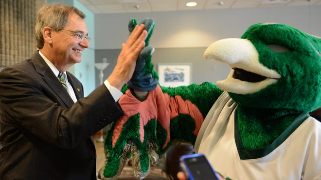Press-Gazette Media reporter Patti Zarling, dressed as UW-Green Bay mascot, Phlash, high-fives with chancellor Gary L. Miller, Wednesday.