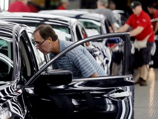 An employee at Nissan's Smyrna plant inspects finished