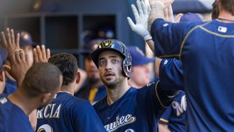 Brewers leftfielder Ryan Braun is greeted in the dugout by teammates after hitting a two-run home run in the seventh inning Wednesday vs. the Rockies at Miller Park.