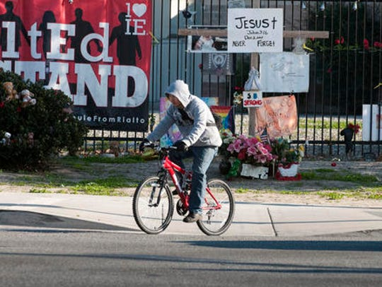 A cyclist passes memorial items displayed at the Inland