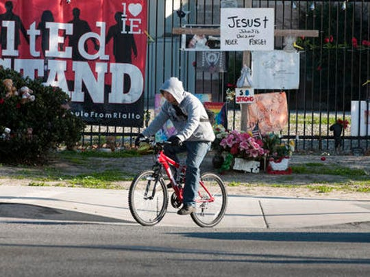 A cyclist passes memorial items displayed at the Inland Regional Center, the site of last year's terror attack, in San Bernardino, Calif., Thursday Dec. 1, 2016. Friday will mark the one year anniversary of the attack.