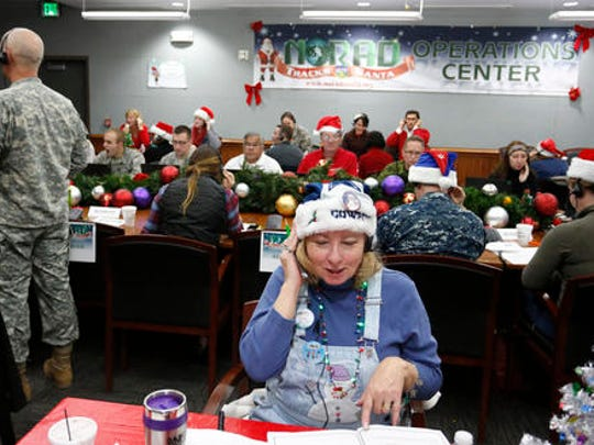 FILE - In this Dec. 24, 2014, file photo, volunteers take phone calls from children asking where Santa is and when he will deliver presents to their house, during the annual NORAD Tracks Santa Operation, at the North American Aerospace Defense Command, or NORAD, at Peterson Air Force Base, in Colorado Springs, Colo. The wildly popular NORAD Tracks Santa operation is launching its 61st run at Peterson Air Force Base, Colorado. Volunteers will answer phone calls and emails and post updates about Santa's storybook world tour on Facebook and Twitter.