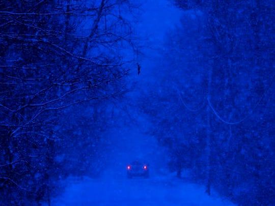 A motorist drives through a snow storm in Durham, Maine,