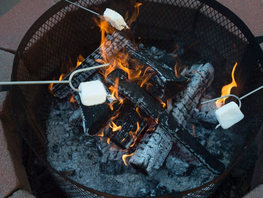 Marshmallows are roasted in a backyard fire pit in