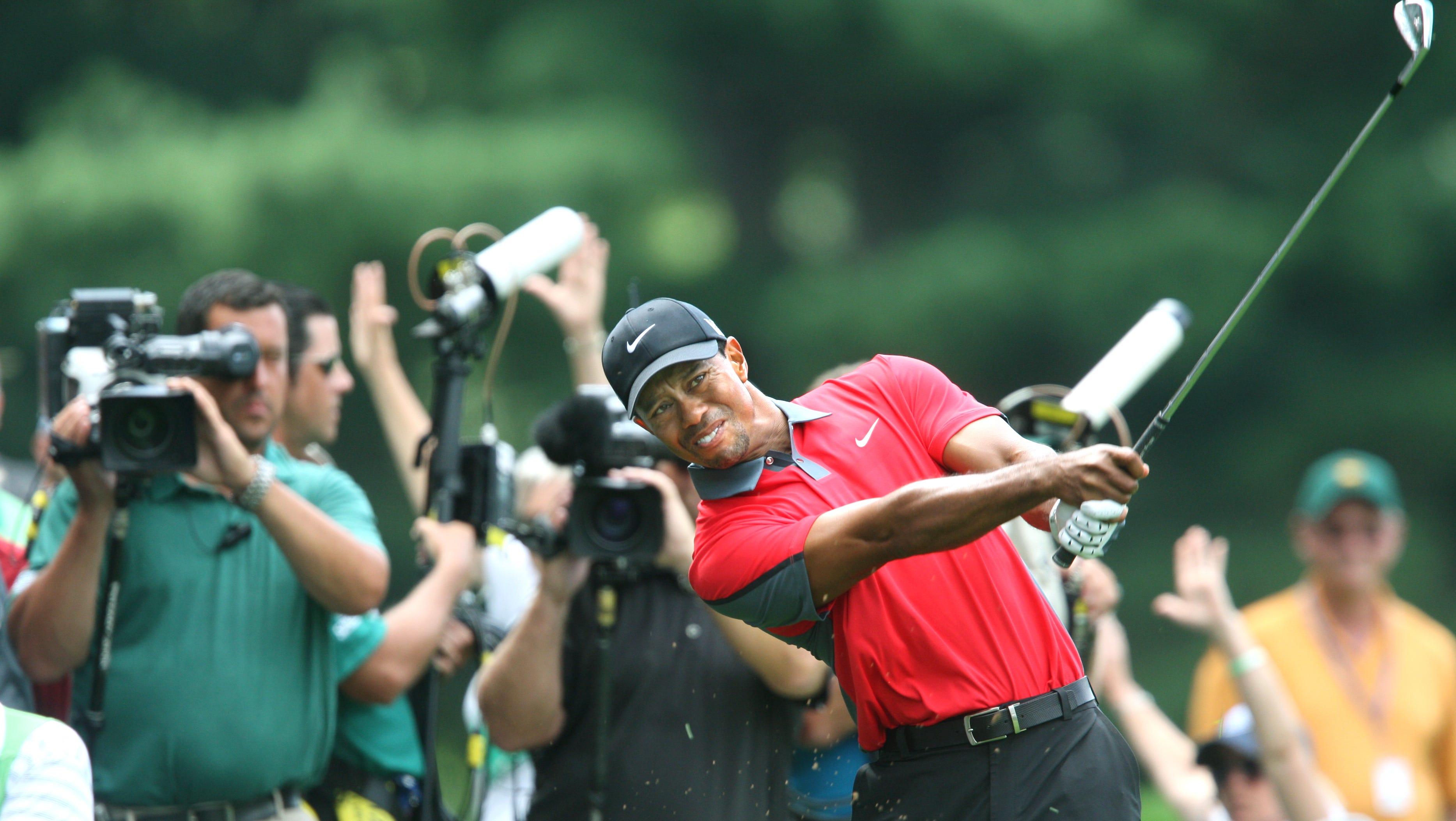 Tiger Woods swings on the 4 fairway.