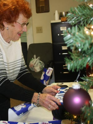 Doris Stortz of Erlanger wraps a gift for a senior during a previous year's Be a Santa to a Senior program at Home Instead Senior Care.