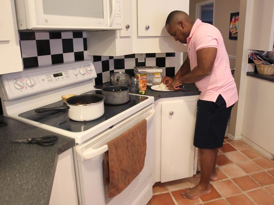 Investment consultant and grill master Braxton Rhone adds chopped onions and Spanish rice to grilled meat as he makes dinner for his family in Fort Myers.