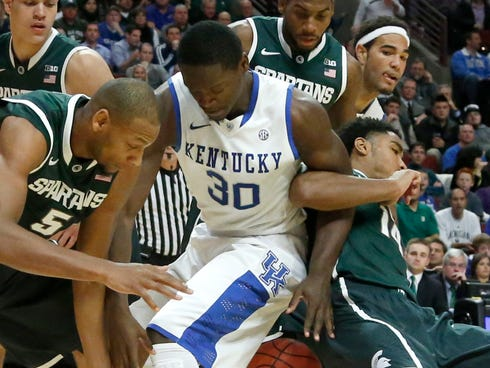 Michigan State center Adreian Payne (5), Kentucky forward Julius Randle (30) and Michigan State guard Gary Harris, right, struggle for a loose ball during the first half of an NCAA college basketball game Tuesday.