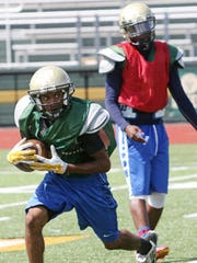 FDR's Kemyero King receives a hand off from Justin Guerrero during preseason practice on Thursday.
