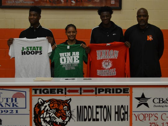 Middleton's Kelan Jones (far left), Sequoya Warren (center left) and Tylandrius Parks (center right) stand with Middleton coach James Burkley (far right) after signing college scholarships.