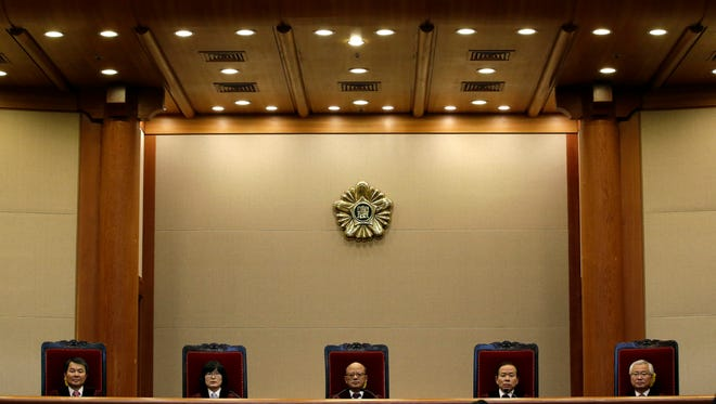 Park Han-chul, center, president of South Korea's Constitutional Court, with other judges Feb. 26, 2015, before announcing that the country's top court was abolishing a 62-year-old law that made adultery a crime.