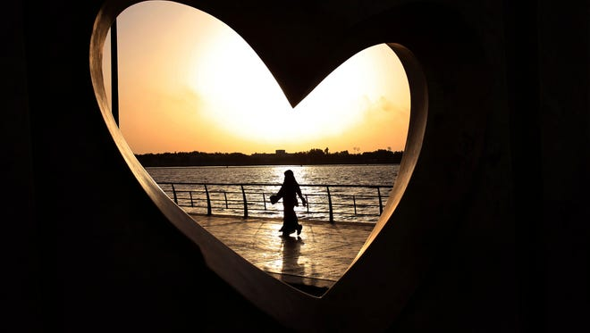 In this May 11, 2014 file photo, a Saudi woman seen through a heart-shaped statue walks along an inlet of the Red Sea in Jiddah, Saudi Arabia.