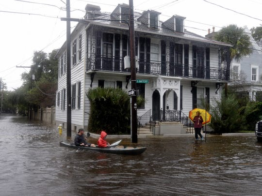 Paul Banker, left, paddles a kayak, with his wife, Wink Banker, as they takes photos on a flooded street in Charleston, S.C., on  Oct. 3.