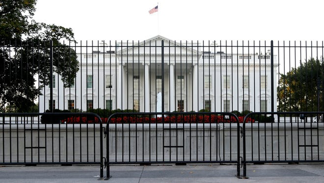 The White House and North Lawn are seen behind a security fence on Pennsylvania Ave. in Washington on Monday, Sept. 22, 2014.