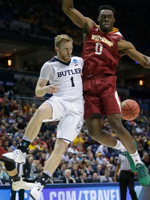 Butler guard Tyler Lewis  passes behind the back of Winthrop center Duby Okeke during their first-round NCAA Tournament game.