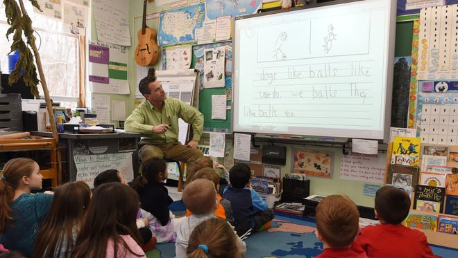 Damian Kortan, a first grade teacher at Overlook Primary School, goes over a writing sample during class.