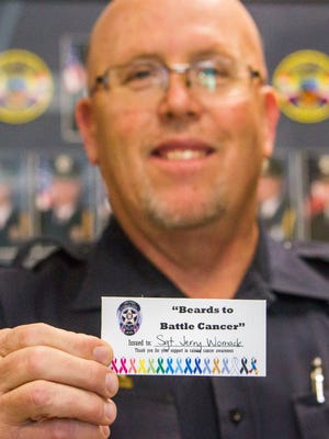 """Cedar City Police Sgt. Jerry Womack holds his """"Beards to Battle Cancer"""" card, Wednesday, Oct. 19, 2016."""