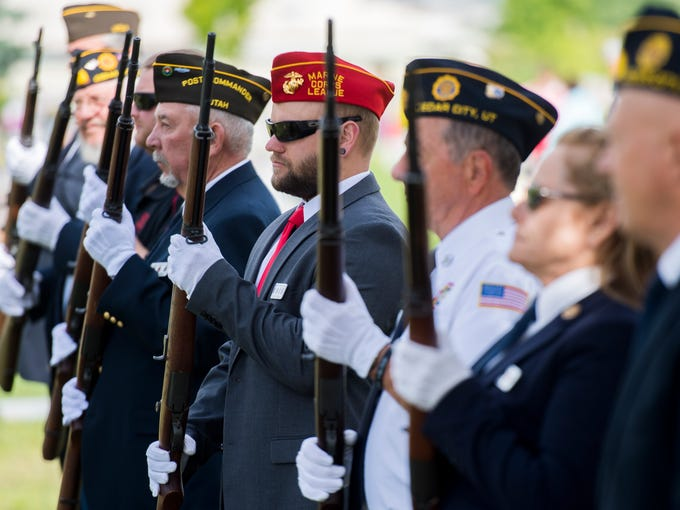Veterans line up for a 21-gun salute during the Memorial
