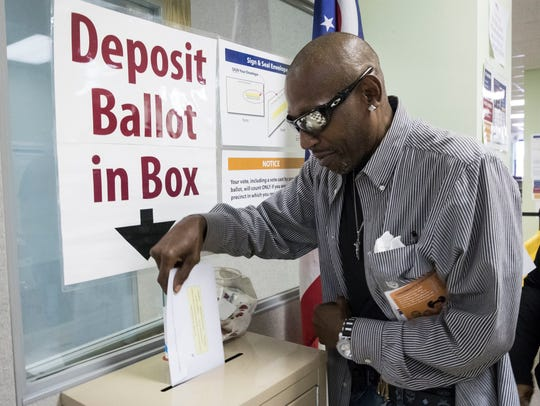 James Chambers deposits his vote into a ballot box