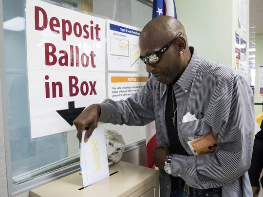 James Chambers deposits his vote into a ballot box at the Hamilton County Board of Elections as early voting begins statewide Oct. 12 in Cincinnati. A political activist on Sunday claimed on Twitter that Donald Trump supporters with dogs harassed voters at a Cincinnati polling place.