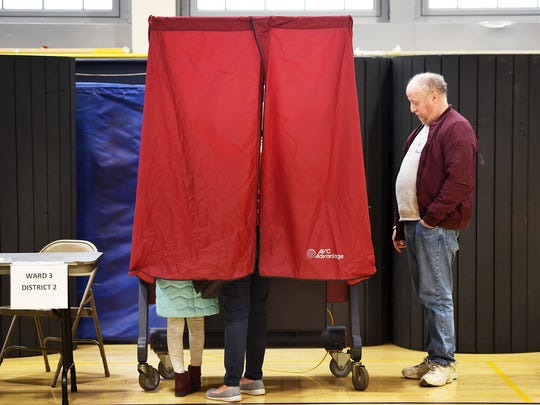 A woman accompanied by a young girl casts her vote at the Hackensack High School gym last November.