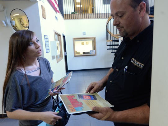 After being recognized by Stephen Eagle (right), Cassie Nygren explains her work posting fliers for Rise Together in the Marinette police station on Thursday, Aug. 7.