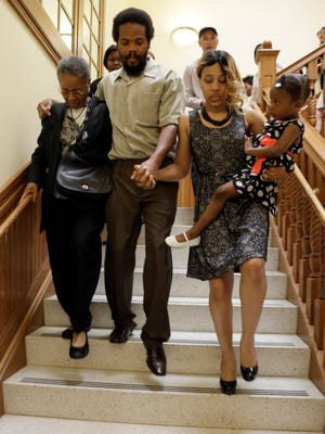 "Cornealious ""Mike"" Anderson walks out of the Mississippi County Courthouse on May 5, 2014, with his grandmother, Mary Porter, left; and his wife, LaQonna Anderson, right; holding their daughter, Nevaeh, 3."