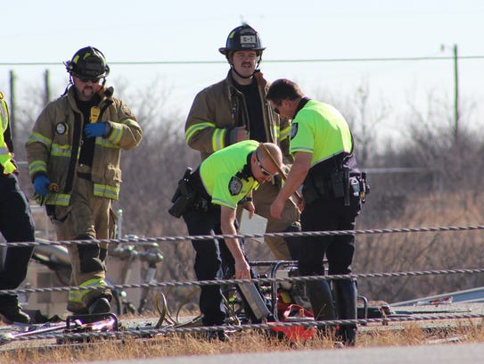 Abilene police and firefighters study debris from a Friday morning crash on Interstate 20 in Abilene that, police report, killed at least two people.