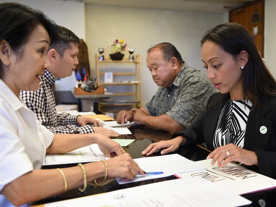 "Regine Biscoe Lee, prospective senatorial candidate, right, and Andy Santiago, running for Umatac mayor, pick up an application packet at the Guam Election Commission office in Anigua on Jan. 28. ""I'm very excited to get out into the villages and meet the people of Guam, and just listen to what they have to say,"" said Lee."